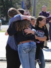 Two women hug before a community prayer vigil for two teens killed Friday night in a crash near Buckeye High School.