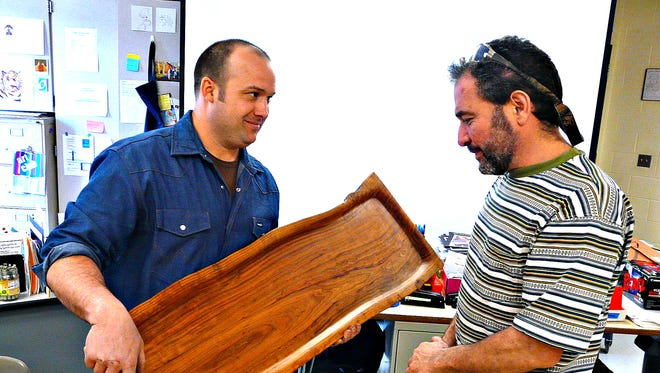 One of Bret Cavanaugh's more-portable creations, a cherry-wood platter, is admired by Del Val wood shop teacher Josh Paul at the school's monthly visiting-artist presentation.
