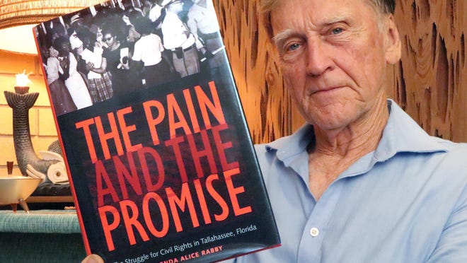 "Oscar Brock Jr. holds a copy of author Glenda Alice Rabby's ""The Pain and the Promise: The Struggle for Civil Rights in Tallahassee, Florida,"" published in 1999. Included in the book is Brock's experience participating in a sit-in on March 12, 1960, that resulted in his arrest."