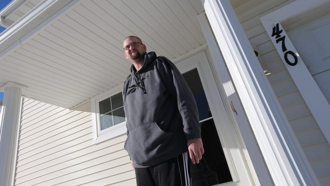 Mark Mitchell stands on the front porch of his Pleasant Hill home, where he was shot at random Nov. 17. Mitchell, who was shot in the stomach, says he considered moving away but has decided not to let the incident rule him.
