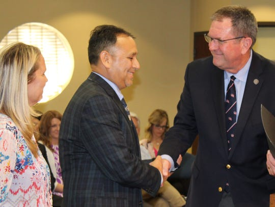 Tim de la Vega is congratulated by state Rep. and former