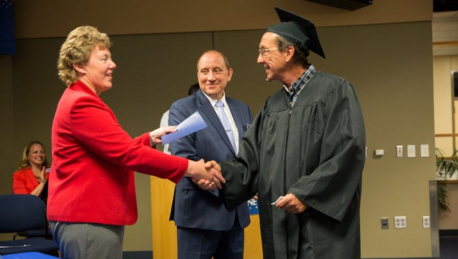Christopher Dietz of Beaver Dam receives his General Education Development (GED) diploma at Moraine Park Technical College's recent GED/HSED graduation ceremony. Handing him his diploma Moraine Park President Bonnie Baerwald, with Jim Eden, vice president of Academic Affairs looking on.