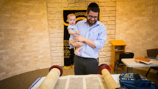 At the Alevy Chabad Jewish Center de Las Cruces, Rabbi Bery Schmukler, holding his 10-month-old daughter, Cherna Schmukler, on Wednesday, July 20, 2016, looks at a Torah rescued from destruction during Kristallnacht by 14-year-old Isaac Schwartz.