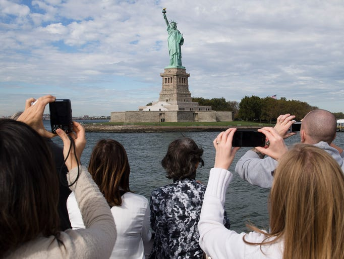 Passengers photograph the Statue of Liberty from a boat that circles famous landmarks on Oct. 12, 2013, in New York Harbor. On Sunday, the Statue of Liberty will reopen to the public after the state of New York agreed to shoulder the costs of running the site during the federal government shutdown.