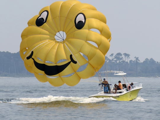 Key Sailing employees prepare to take customers parasailing on the Santa Rosa Sound off of Quietwater Beach in 2012. A new law governing the operation of parasailing companies goes into effect today.