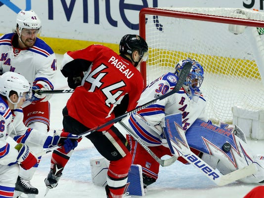 New York Rangers goaltender Henrik Lundqvist (30) makes a pad save as teammates Brendan Smith (42) and Jimmy Vesey (26) try to check Ottawa Senators' Jean-Gabriel Pageau (44) during the second period of an NHL hockey game in Ottawa on Saturday April 8, 2017.  (Fred Chartrand/The Canadian Press via AP)