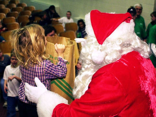 Santa handing out bags of toys to the 625 children attending the Goodfellows Christmas party at South Junior High auditorium. Entertainment at the party was provided by puppets from a First Baptist Church Sunday School class and Henderson Fire Department. (Gleaner photo by Mike Lawrence) 12/23/99