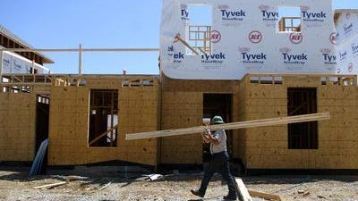 Lester Fisher carries materials in front of a new home under construction at the former Sheppard Square site.