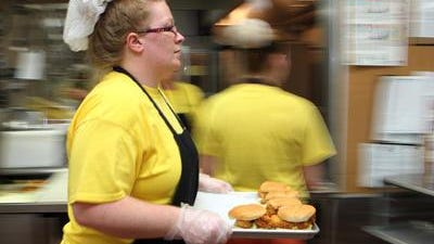 Brandi Hymer, a trainee in a Frisch's Restaurant program at River City Correctional Center, hustles through the kitchen with a tray of fish sandwiches at the facility where she and others are preparing lunch for inmates housed there.