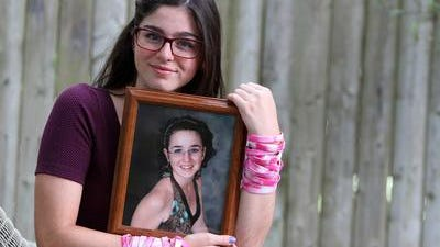 Maggi Brown holds a portrait of her sister Caiti.