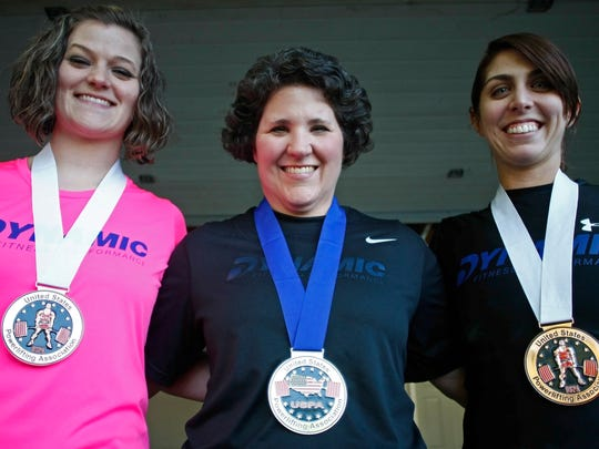 Samantha Forster (from left), Kerry Matson and Arika Howell are members of the BarBelles. a powerlifting group, that train with Michael Howell at his East Salem home on Wednesday. Samantha Foster, Kerry Matson and Arika Howell all medaled in a recent competition.