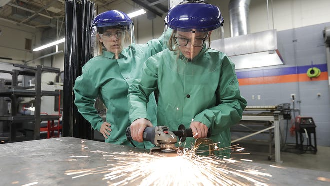 Julia Durant and her daughter Ivy work on a steel yard sculpture during the This Girl Can workshop at Bay Link Manufacturing at West High School. The workshop aims to give girls a chance to learn about the manufacturing industry.