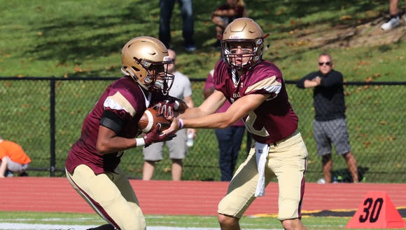 Iona Prep quarterback Derek Robertson hands off to