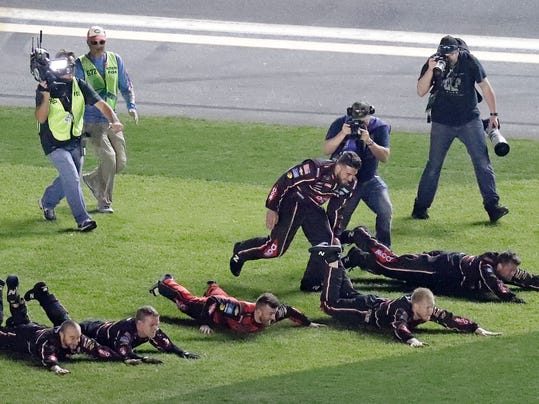 Austin Dillon, center, celebrates with his crew as they dive on the grass in the infield after winning the NASCAR Daytona 500 auto race at Daytona International Speedway, Sunday, Feb. 18, 2018, in Daytona Beach, Fla. (AP Photo/John Raoux)