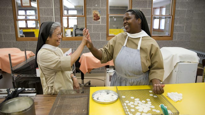 Poor Clares nuns Sister Maria Eden, left, and Sister Thereza share a laugh as they make altar bread, also known as communion wafers, at the Monastery of Saint Clare in Langhorne, Pa.