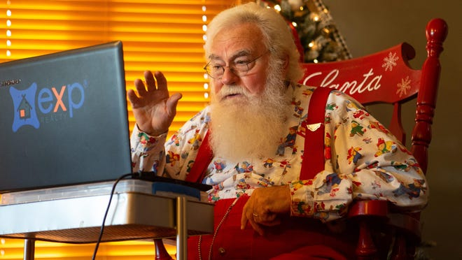 Santa Ken Sutton waves to boys and girls as he interacts with them Tuesday afternoon over Zoom.