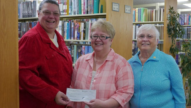 Roberta DeVetter, at left, president of the Marshfield Noon Rotary Club, from left, Lori Belongia, library director, and Ginny Mazza, one of the Capital Campaign Co-Chairs and Noon Rotary member, were all smiles during donation presentation.