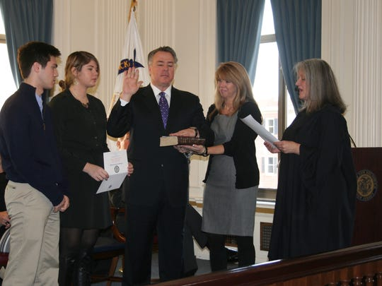 New Brunswick Municipal Court Judge Mary Casey (right) administers the Oath of Office to New Brunswick Councilman Kevin Egan (center) on Friday.