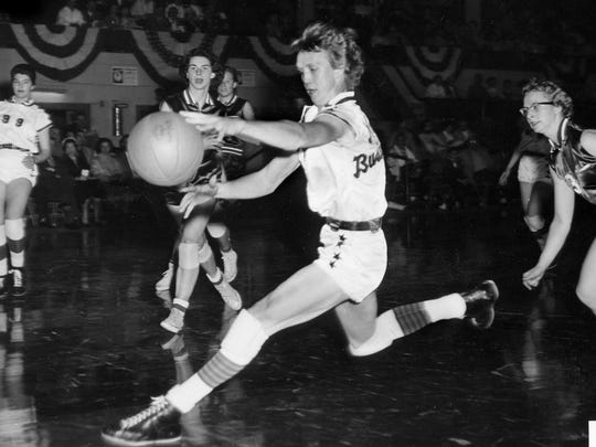 Nera White, center, of Nashville Business College, reaches for the ball during a game in St. Joseph, Mo., in 1960.