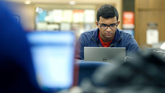 Sanjeev Sekharan, an accounting major, studies in the library at St. John Fisher College in Pittsford.