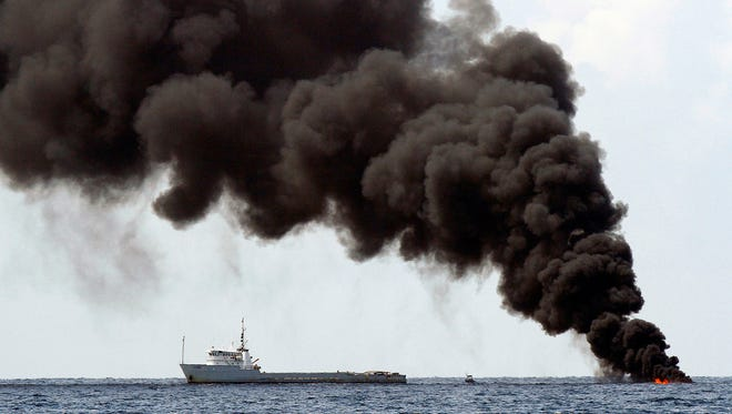 Smoke rises from a controlled burn of contained oil from the Deepwater Horizon oil well leak on the Gulf of Mexico near the coast of Louisiana 0n July 16, 2010.