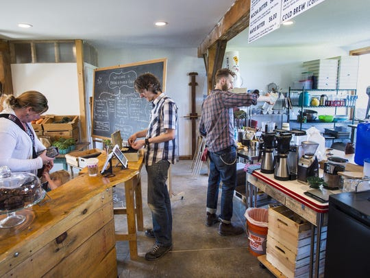 Chris Dorman, left, of Bread and Butter Farm, helps a farm store customer while Mike Proia makes an order at the Blank Page Cafe in Shelburne on Friday, May 20, 2016. Bread and Butter Farm encompasses several small enterprises under one roof.