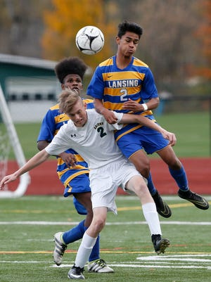 Lansing's Langston Hopkins goes up for a header over Greene's Nick Shoemaker during Wednesday's Section 4 Class C semi-final game at Greene Central School on October 25, 2017.