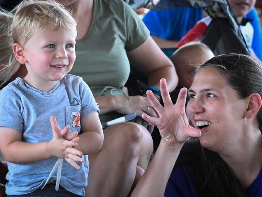 Connor Thompson, 2, and his mother Susan Thompson find out the program involves dinosaurs as the pair watch the music-telling troupe Tales & Scales present the story of T-Rex during the Henderson Public Library's Reading in the Park at Freedom Park Tuesday.