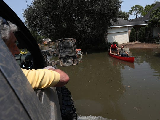 Joe Turano, 87, talks to neighbors on a boat as rides in a truck to his flooded home on Sept. 6 in Houston, Texas. Houston flooding occurred in the wake of Hurricane Harvey. Troops from Malmstrom recently returned to Montana after volunteering to help get victims aid in Texas.