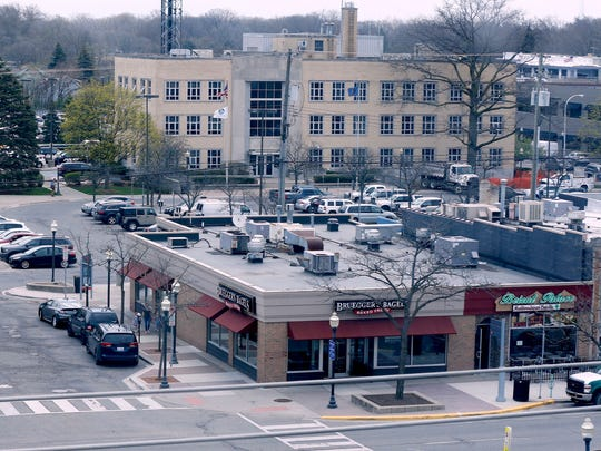 The current view of South Main Street in Royal Oak, looking east toward a bagel shop as well as other storefronts and, beyond them, the current city hall building.