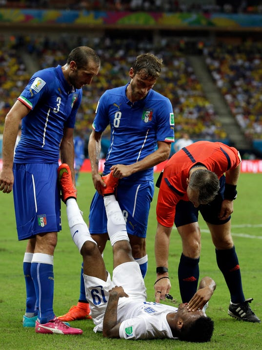 Italy's Giorgio Chiellini, left, and Claudio Marchisio, center, assist England's Raheem Sterling to stretch during the group D World Cup soccer match between England and Italy at the Arena da Amazonia in Manaus, Brazil, Saturday, June 14, 2014. (AP Photo/Martin Mejia)