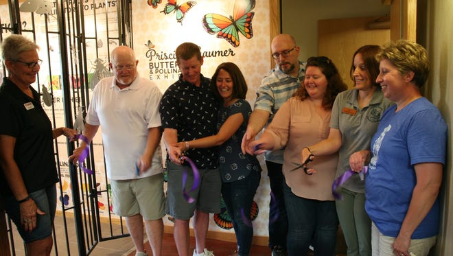 Priscilla Gaumer's family cuts the ribbon at the grand opening of the Priscilla Gaumer Butterfly and Pollinator Exhibit at the Annett Nature Center in rural Warren County. Holding scissors from left to right are Priscilla's husband Ben Gaumer, their son Doug Gaumer and his wife Heather, Greg Hoffman and his wife Hillary Hoffman (Gaumer) and Warren County naturalist Karen Johlas Szalkowski.