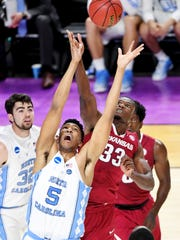 UNC forward Tony Bradley (5) and Arkansas forward Moses Kingsley (33) reach for the ball during the 2nd round of the NCAA Tournament at Bon Secours Wellness Arena in downtown Greenville on Sunday, March 19, 2017.