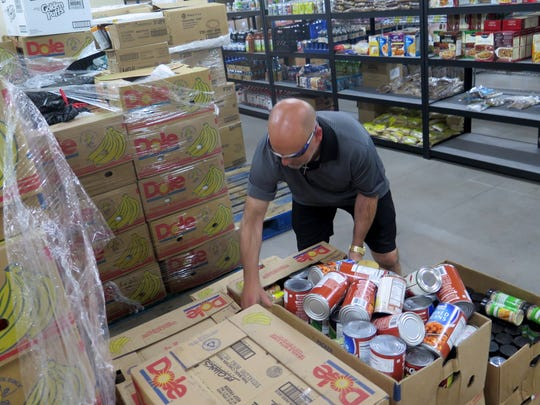 Volunteer Scott Williamson works to sort through boxes of food at the SwitchPoint food pantry in St. George on Friday, Aug. 4, 2015.