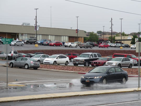 A car splashes through a low spot on 100 South in St. George near Dixie State University on Monday.