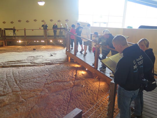 Visitors peer over the surface of the uncovered dinosaur tracks and other prehistoric clues left at the Dinosaur Discovery Site at Johnson Farm in St. George on Saturday, May 8, 2016.