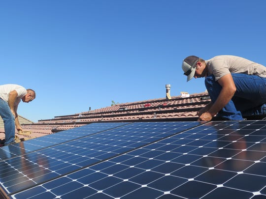 Installers with Legend Solar work to add solar panels