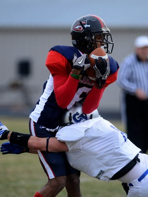 Gladiators receiver Marshane Haynes makes a catch as Gallatin Valley's Ron Kurschner makes a tackle during a 2012 RMFL game at Memorial Stadium.