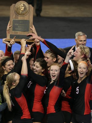 Harlan players celebrate winning the 2013 Class 4-A state volleyball title.