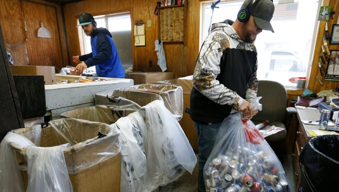 Josh Thompson, right, ties up a full bag of cans as Ben Allen continues sorting Thursday, March 16, 2017, at the Kans R Us redemption center in Perry, Iowa.