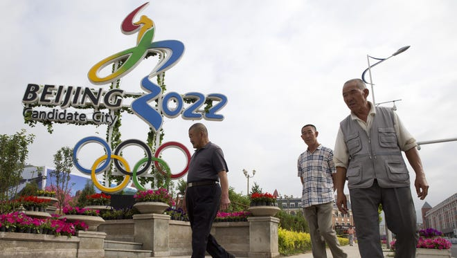 Chinese men walk past the Beijing 2022 Olympic bid logo on Aug. 1 in the mountain town of Chongli, which will host the 2022 Nordic skiing, ski jumping, and other outdoor Winter Olympic events in northern China's Hebei province. Beijing made history as the first city to win hosting rights for both the Summer and Winter Olympics.