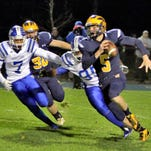 Hartland quarterback Noah Marshall tries to outrun a pair of Western defenders during last year's Lakes Conference championship game, which the Warriors won.