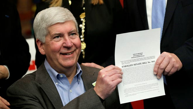 Michigan Gov. Rick Snyder poses for a photograph after signing legislation that establishes comprehensive regulations for the testing, use and eventual sale of autonomous vehicle technology at the Automotive Hall of Fame in Dearborn in December 2016.