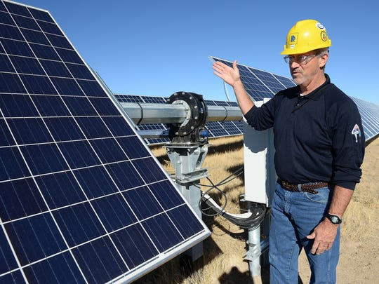 Plant Operations Manager Bobby Redwood points out the torque tube system that moves the solar panels at Rawhide Energy Station on Thursday. The Rawhide Flats Solar Project was completed in October and will produce energy equivalent to the average use of about 8,000 homes.