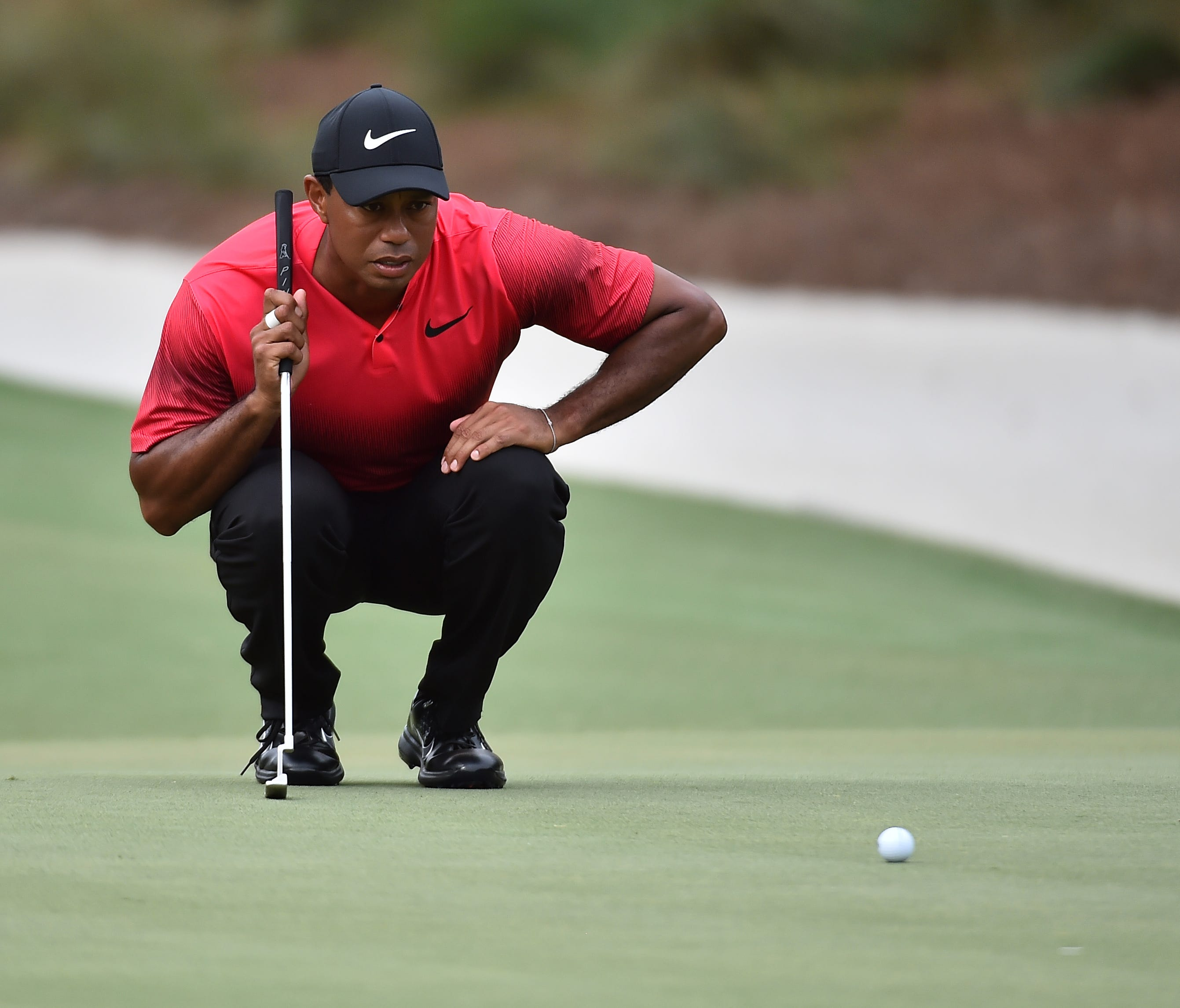 Tiger Woods lines up a putt on the 14th green during the final round of The Players Championship.