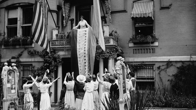 In this Aug. 19, 1920, photo made available by the Library of Congress, Alice Paul, chair of the National Woman's Party, unfurls a banner after the ratification of the 19th Ammendment, from a balcony at the NWP's headquarters in Washington, DC.