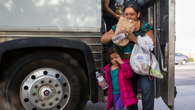 Migrants get off a federal bus after being released by ICE at the Greyhound bus station in Phoenix on June 2, 2014.