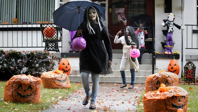 Ameria Williams (from left), Nyanza Smith and Amnesia Blathers go trick-or-treating in the 2000 block of N. Hi Mount Blvd. in Milwaukee on Oct. 31, 2015.
