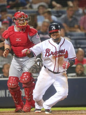 Atlanta Braves' Erick Aybar (1) falls to the ground after being hit by a pitch from Cincinnati Reds reliever Blake Wood during the sixth inning of a baseball game Monday, June 13, 2016, in Atlanta. Reds catcher Tucker Barnhart is at left. Aybar remained in the game.