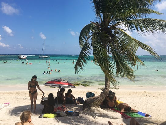 Tourists spend time on Akumal Beach Tuesday, April